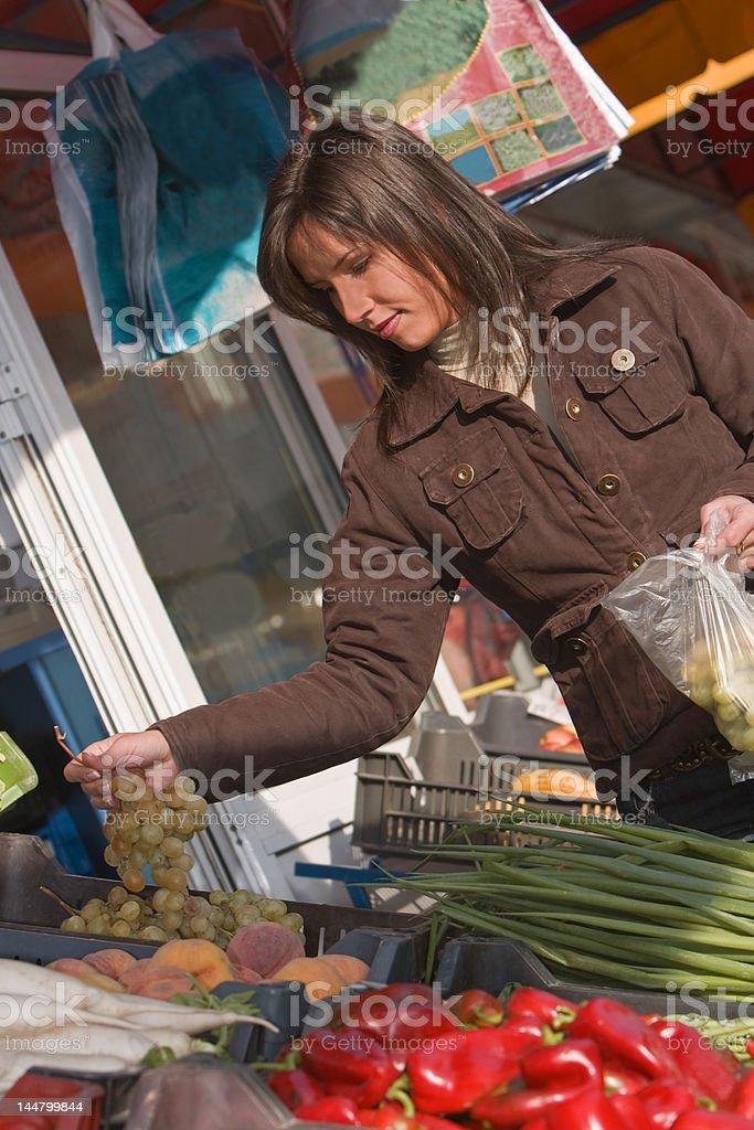Woman buying grapes royalty-free stock photo