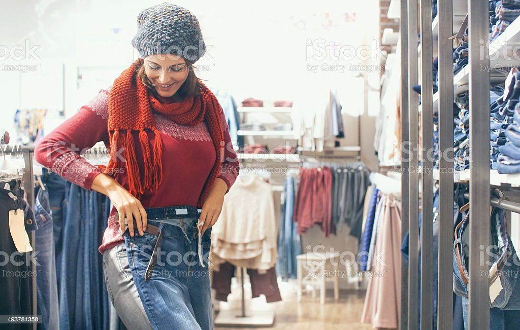Woman buying jeans at retail store. stock photo