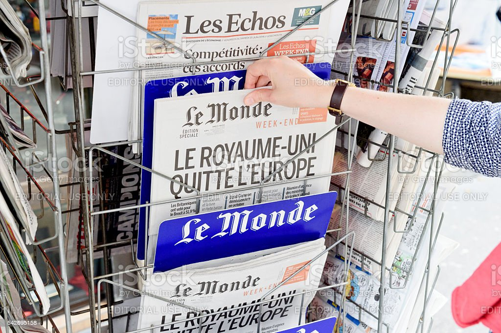 Woman buying Le Monde newspaper about Brexit stock photo