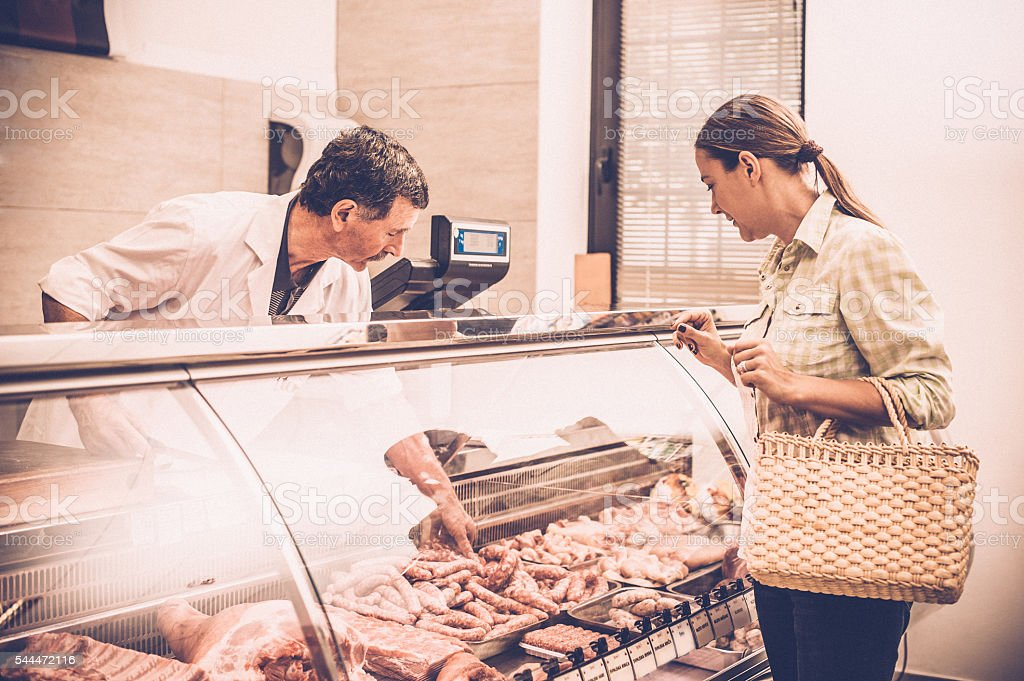 woman buying meat at the butcher shop stock photo