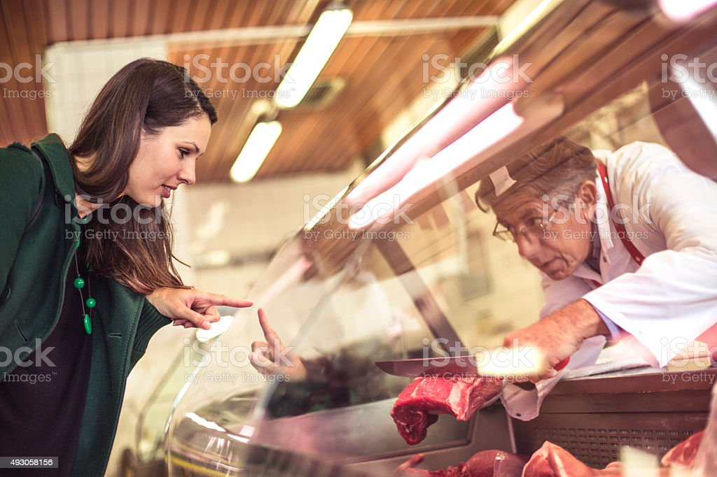 Woman buying meat at the butcher shopp stock photo