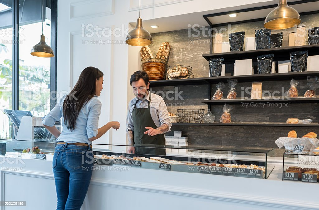 Woman buying pastries at a bakery stock photo