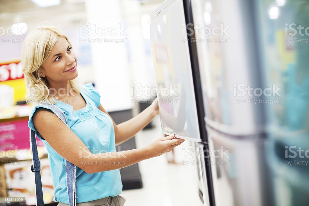 Woman buying refrigerator in a store. stock photo