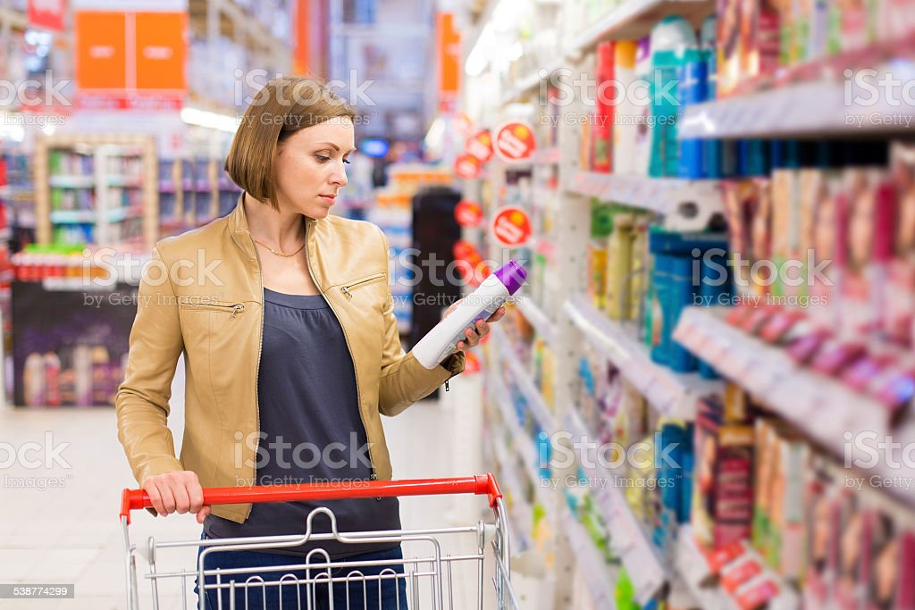 woman buying shampoo stock photo