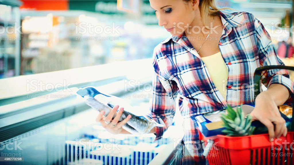 Woman buying some frozen food in supermarket. stock photo