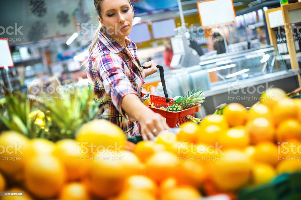 Woman buying some fruit in supermarket. stock photo
