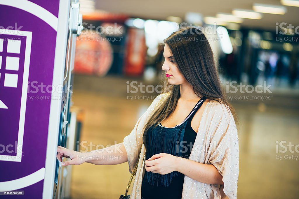 woman buying subway ticket from ticket machine stock photo