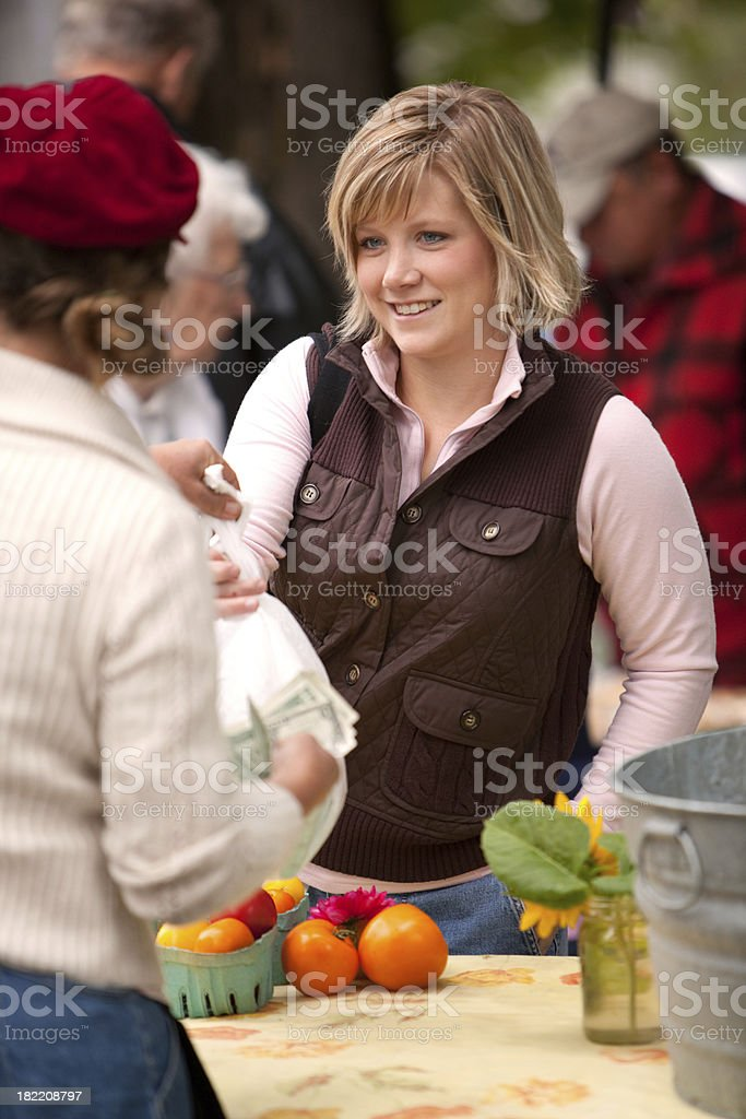 Woman buying tomatoes at a farmers market royalty-free stock photo