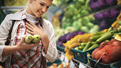 Woman buying veggies in a supermarket.