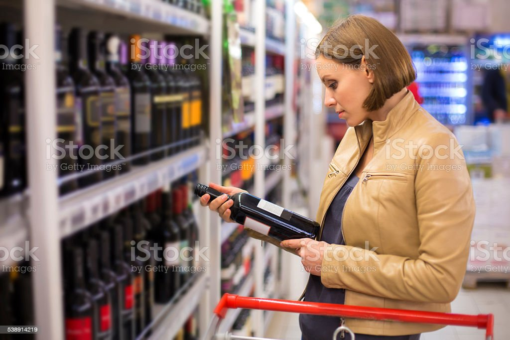 woman buying wine in the supermarket stock photo