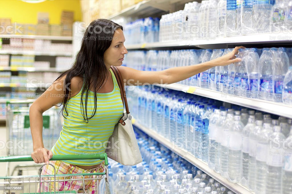 woman buys a bottle of water in the store royalty-free stock photo