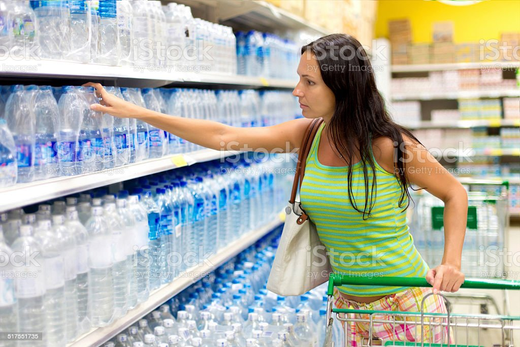 woman buys a bottle of water in the store stock photo