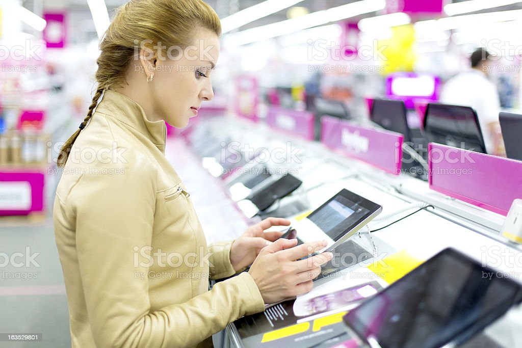 Woman buys a digital tablet. royalty-free stock photo