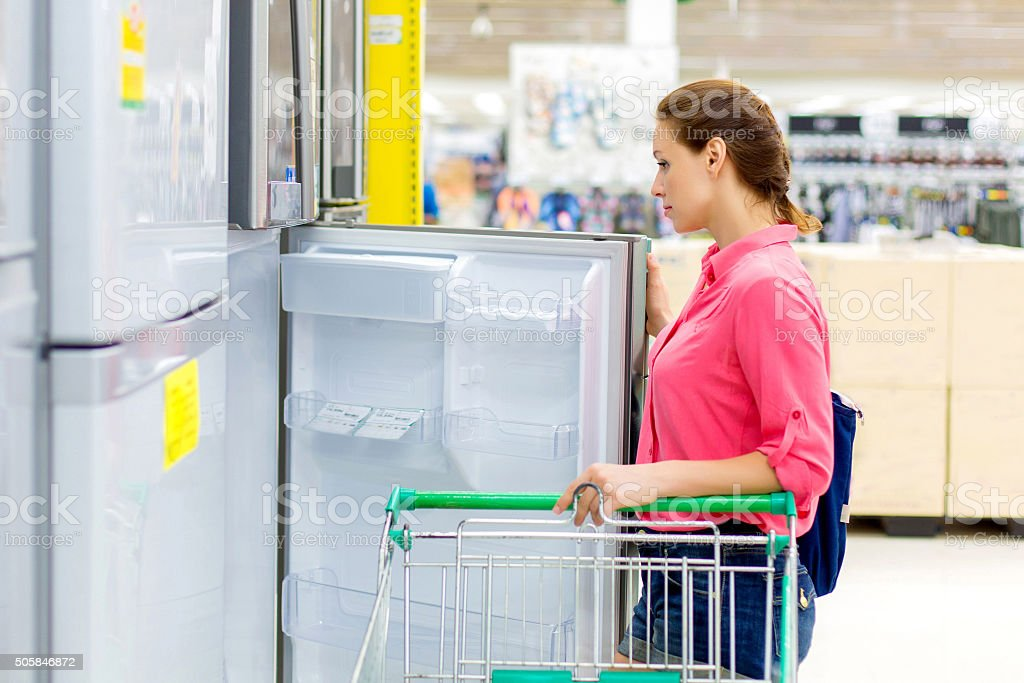 woman buys a refrigerator in the store stock photo