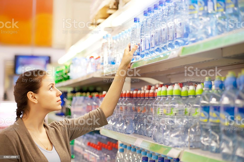 woman buys a water bottle in shop stock photo