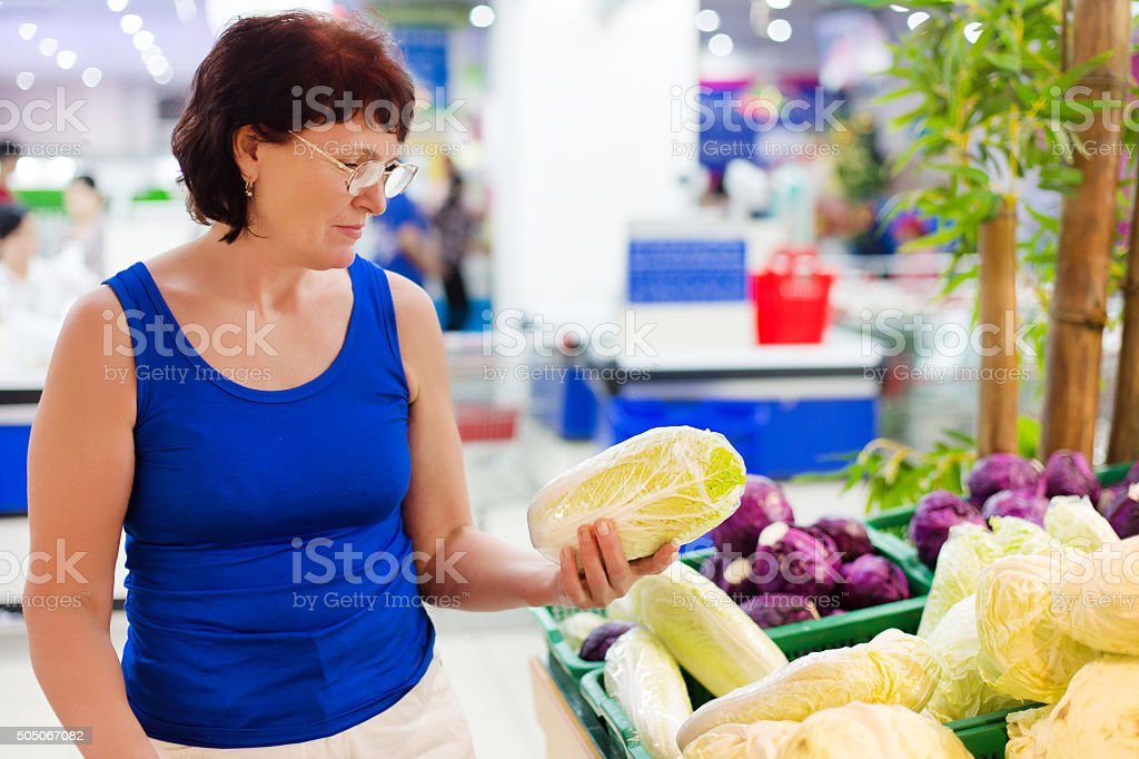 woman buys cabbage stock photo
