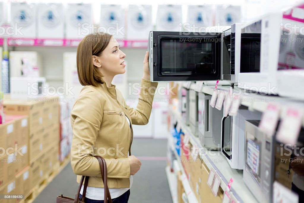 woman buys the microwave stock photo