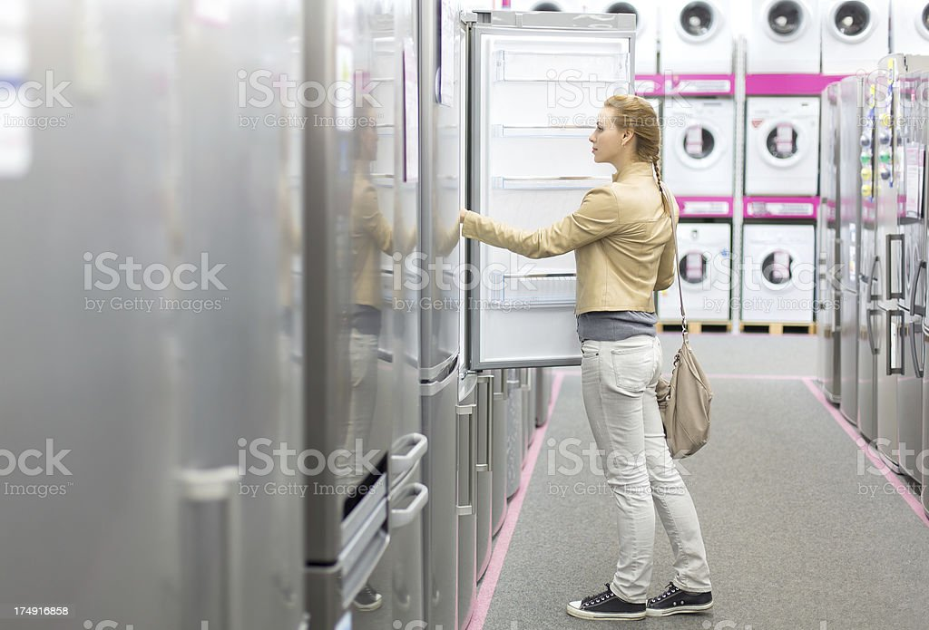woman buys the refrigerator in shop royalty-free stock photo