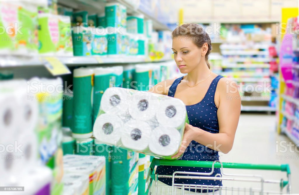 woman buys toilet paper in the supermarket stock photo