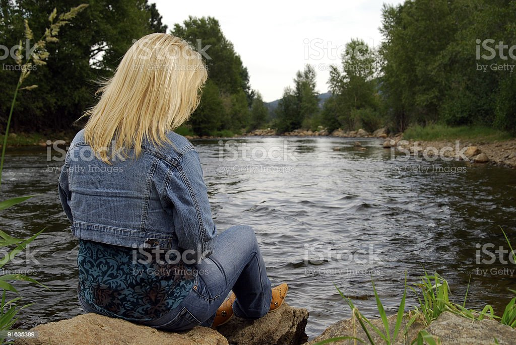Woman by a mountain stream stock photo