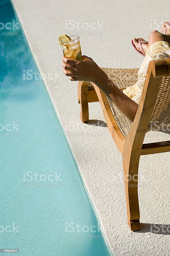 Woman by pool with drink stock photo