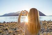 Woman by the lake makes heart shape finger frame