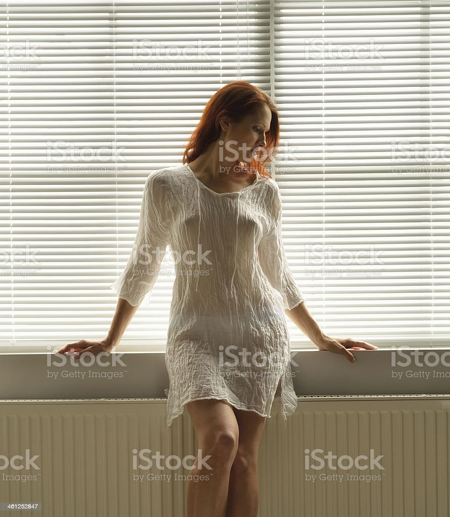 Woman by the window at home stock photo
