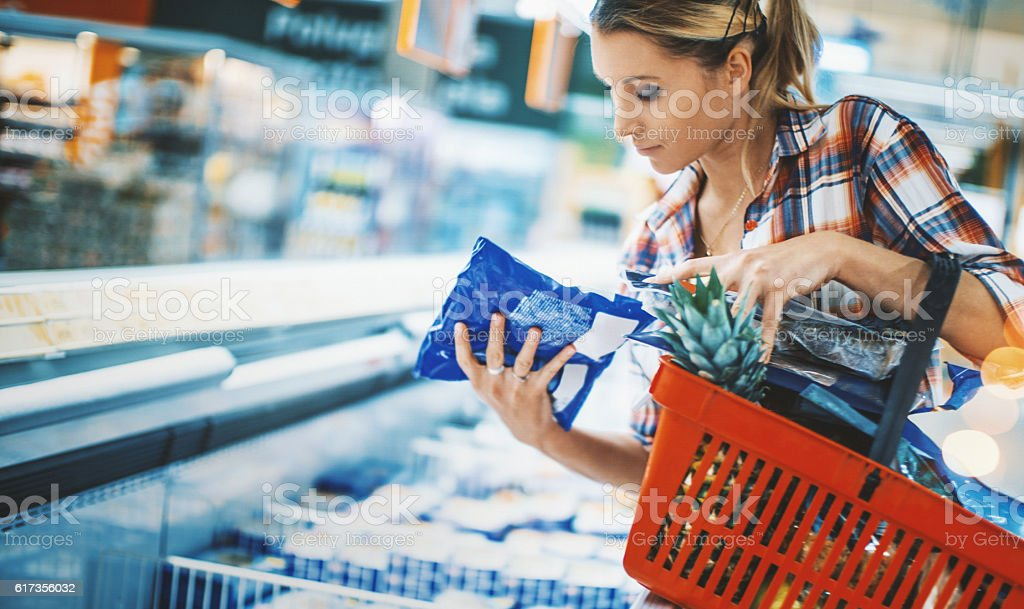 Woman bying some frozen food at a supermarket. stock photo