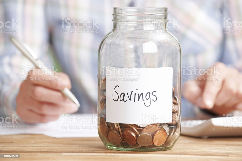 Woman Calculating Budget With Savings Jar In Foreground royalty-free stock photo