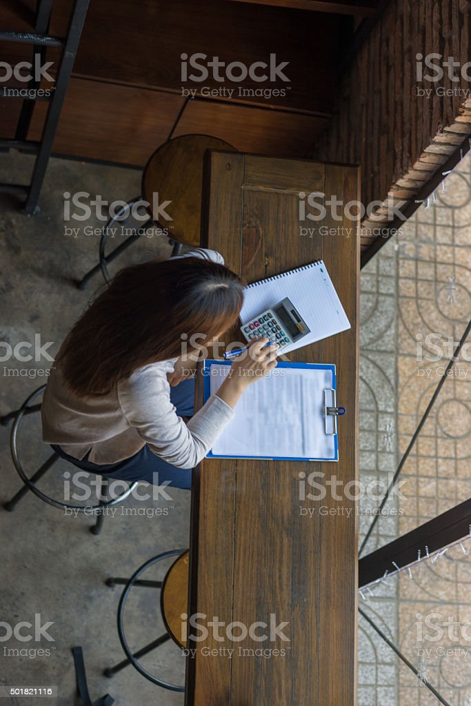 Woman calculating monthly expense of the store stock photo