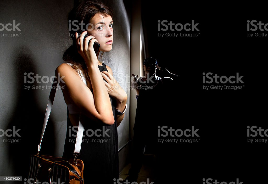 Woman Calling 911 for Help in an Alley stock photo