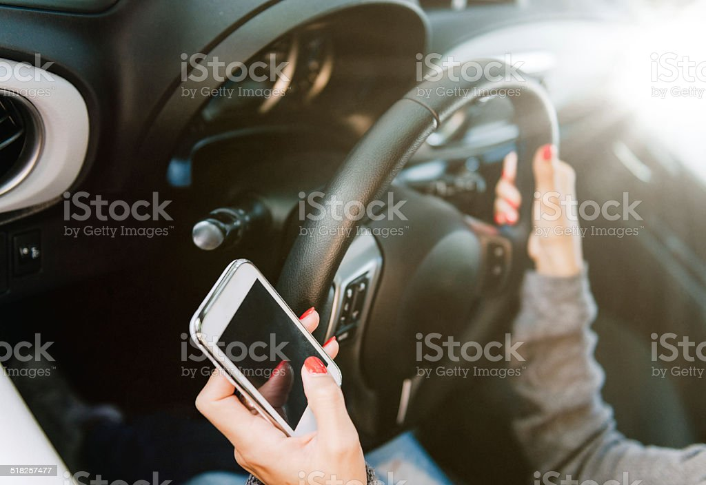 Woman calling for assistance on smart phone while driving vehicle stock photo