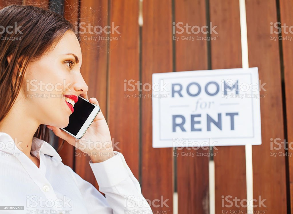 woman calling in front of 'Room for rent' sign stock photo