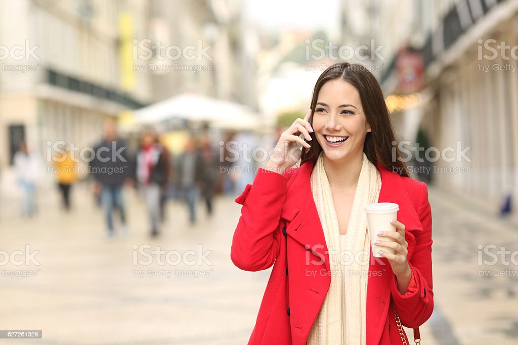 Woman calling on phone walking in the street stock photo