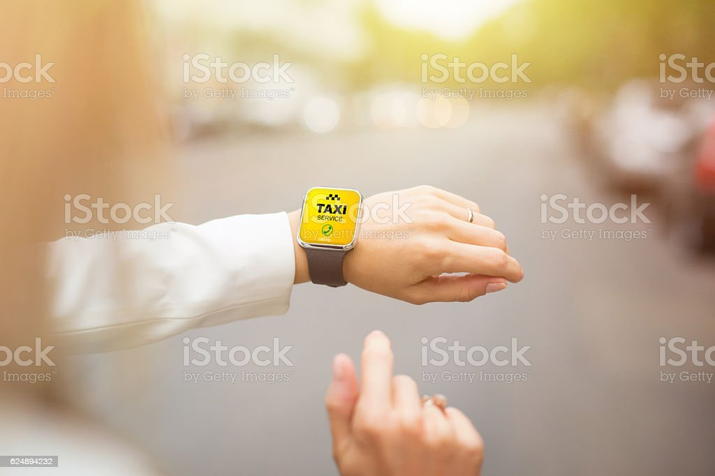Woman calling taxi using her smartwatch stock photo