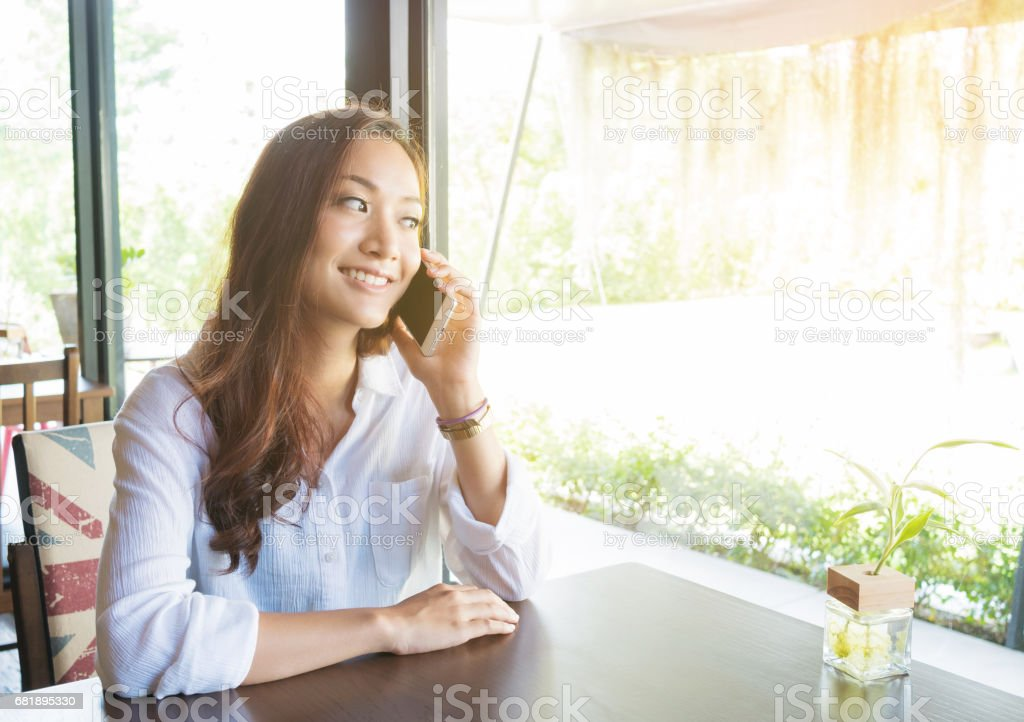 Woman calling with mobile phone in coffee shop stock photo