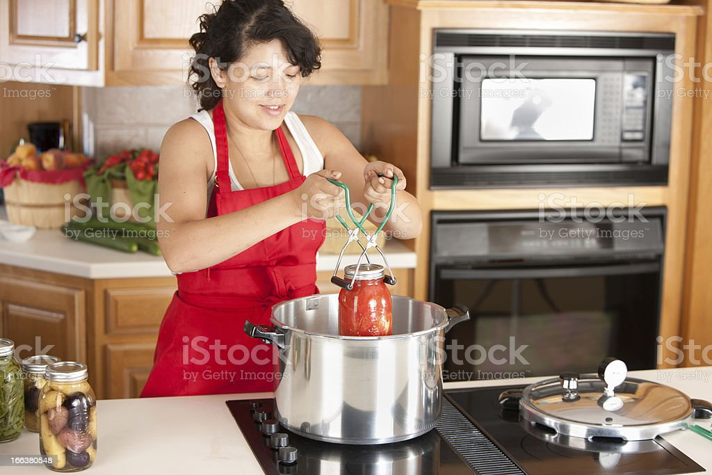 Woman canning tomatoes in her kitchen stock photo