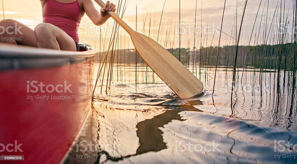 Woman canoeing at sunset stock photo