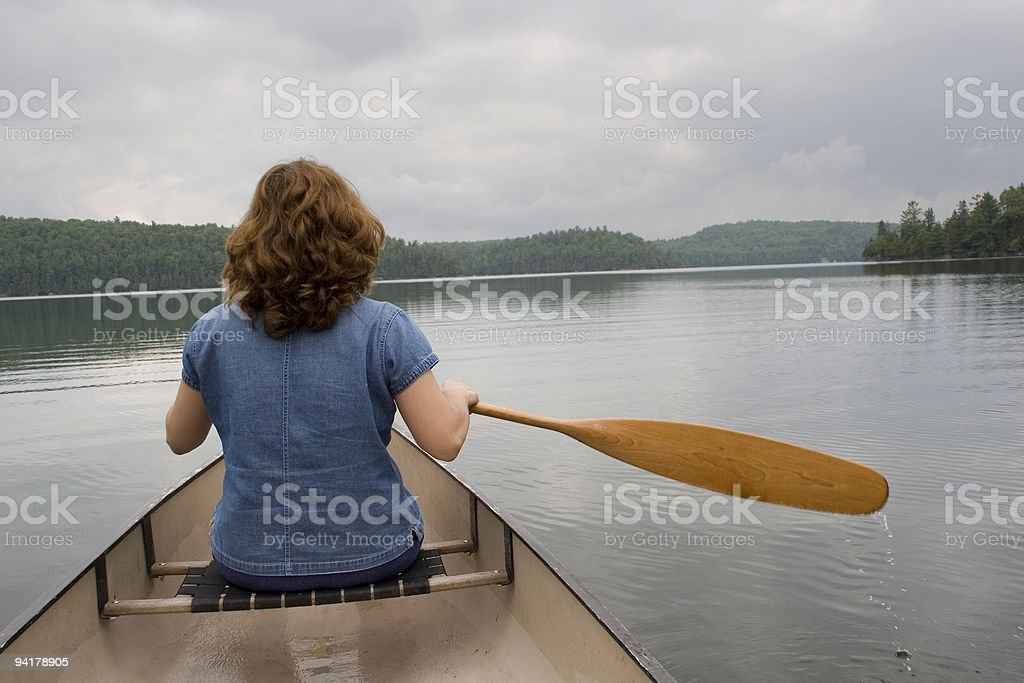 Woman canoeing on a lake royalty-free stock photo