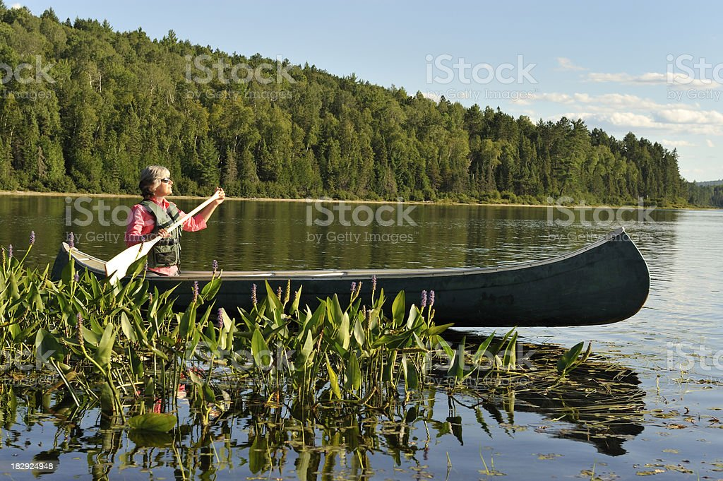 Woman canoeing on lake, beautiful landscape, tranquil outdoor scene. stock photo