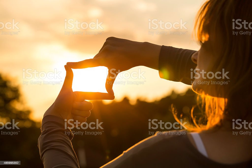 woman capturing the sunset with fingers stock photo