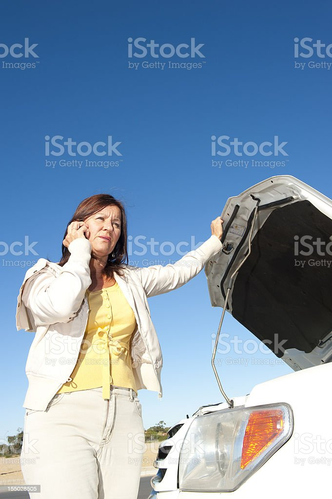 Stressed mature woman breakdown with car on remote road calling for...