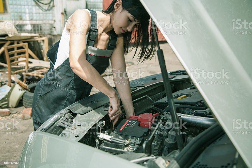 Woman car mechanician repairs engine of car stock photo