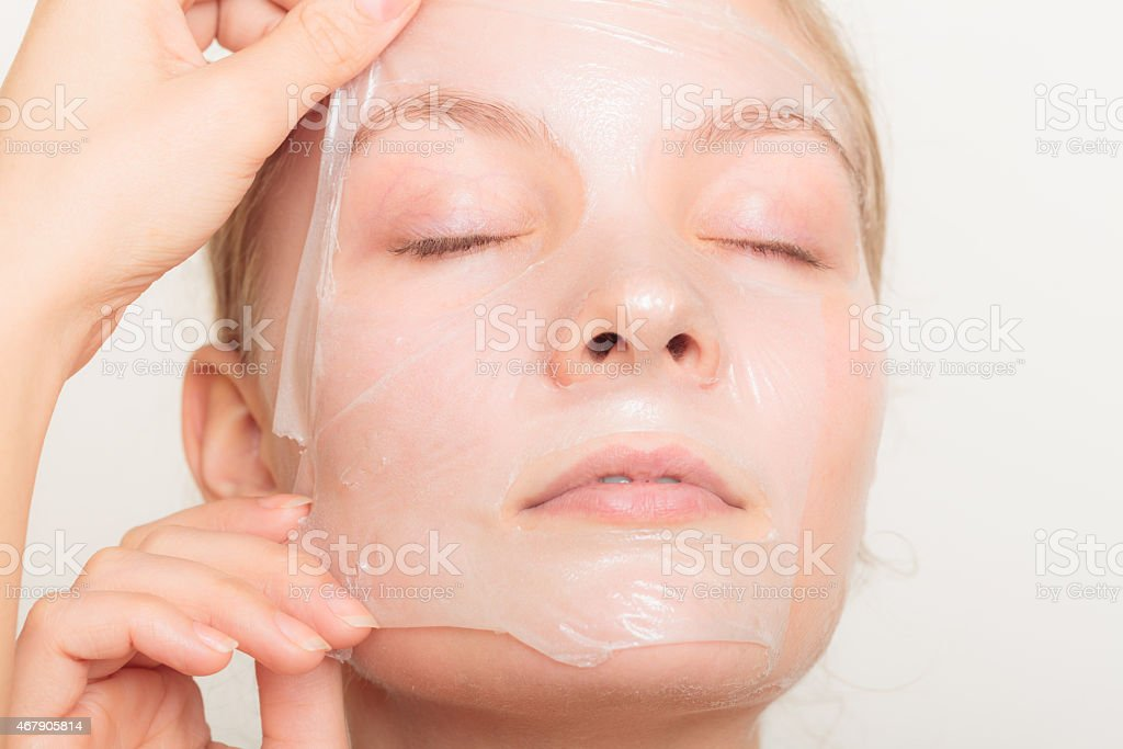 Woman carefully removing a thin mask off her face stock photo