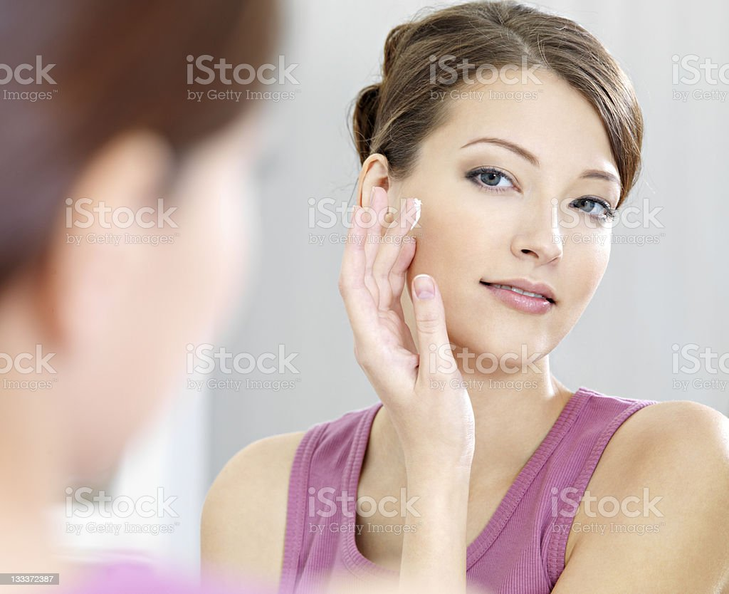 Woman caring of her  beautiful skin on the  face stock photo