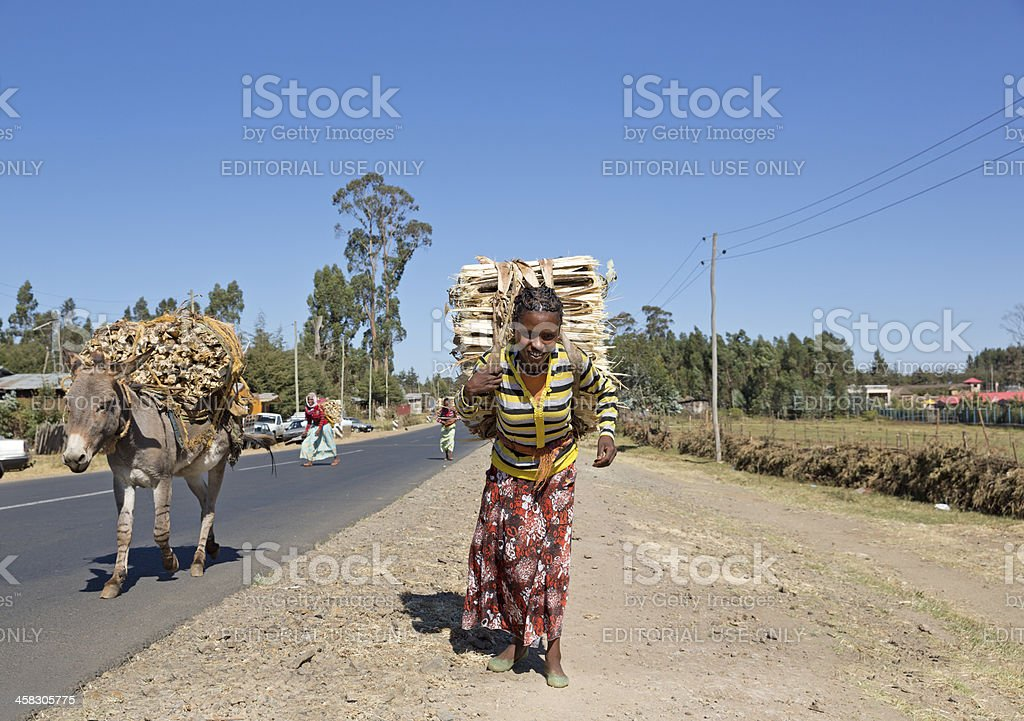 Woman carries wood to market royalty-free stock photo