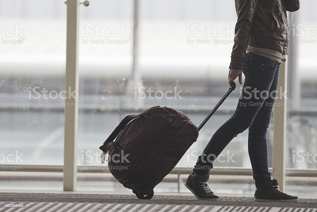 Woman carries your luggage at the airport terminal stock photo