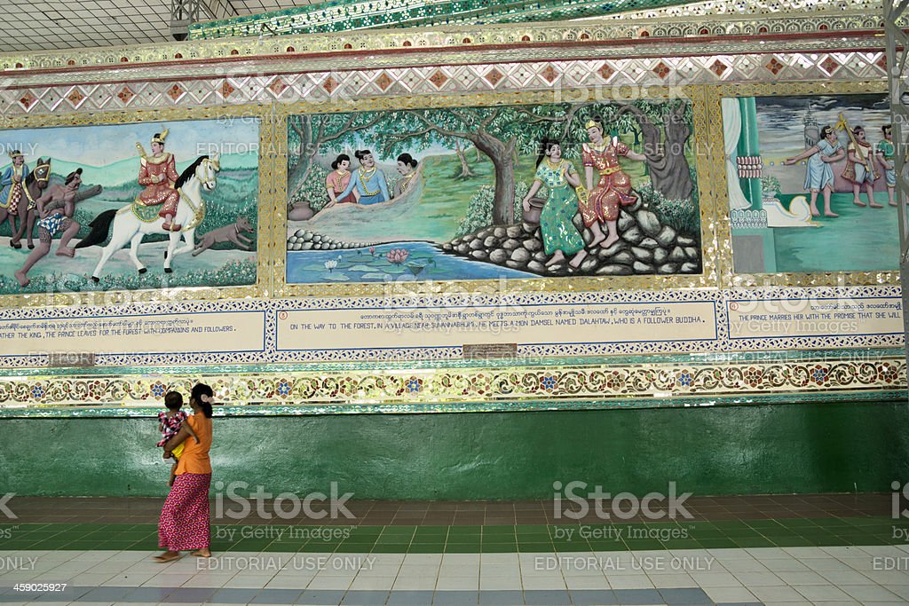Woman carrying a child while walking in temple stock photo