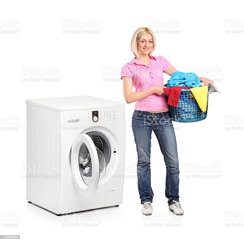 Woman carrying a laundry basket and washing machine royalty-free stock photo