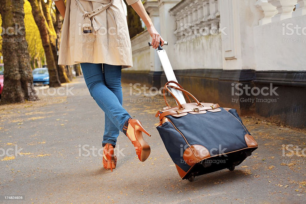 Woman carrying a luggage stock photo